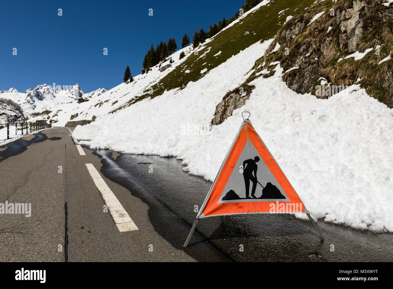 Warning sign because of a road blocked by a snow slide in the Alps - Stock Image