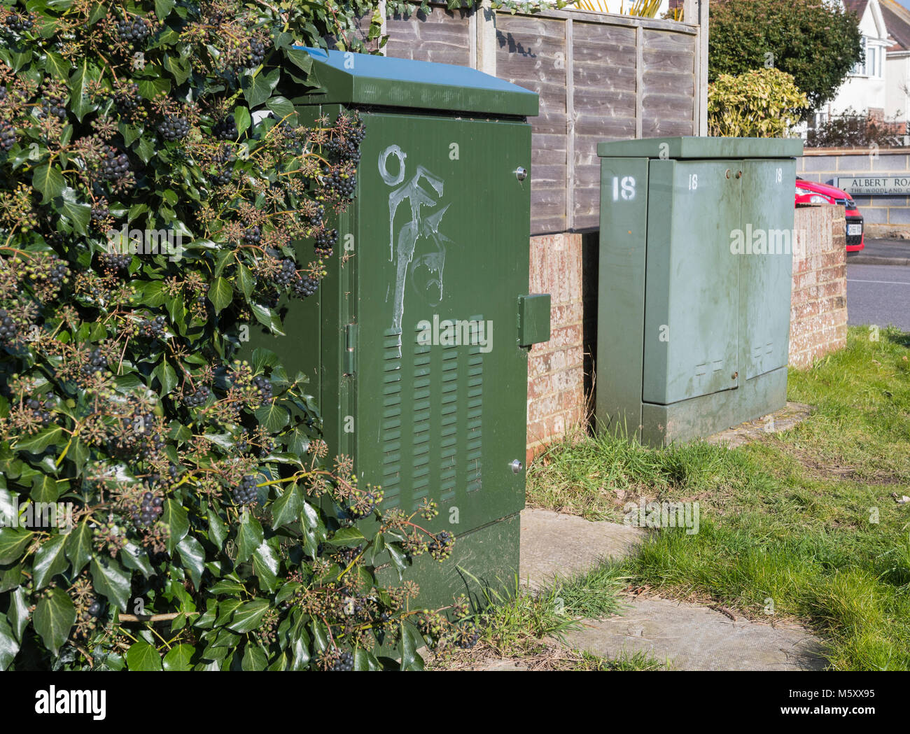 Pair of green British Telecom telephone cabinets on a street corner in England, UK. - Stock Image