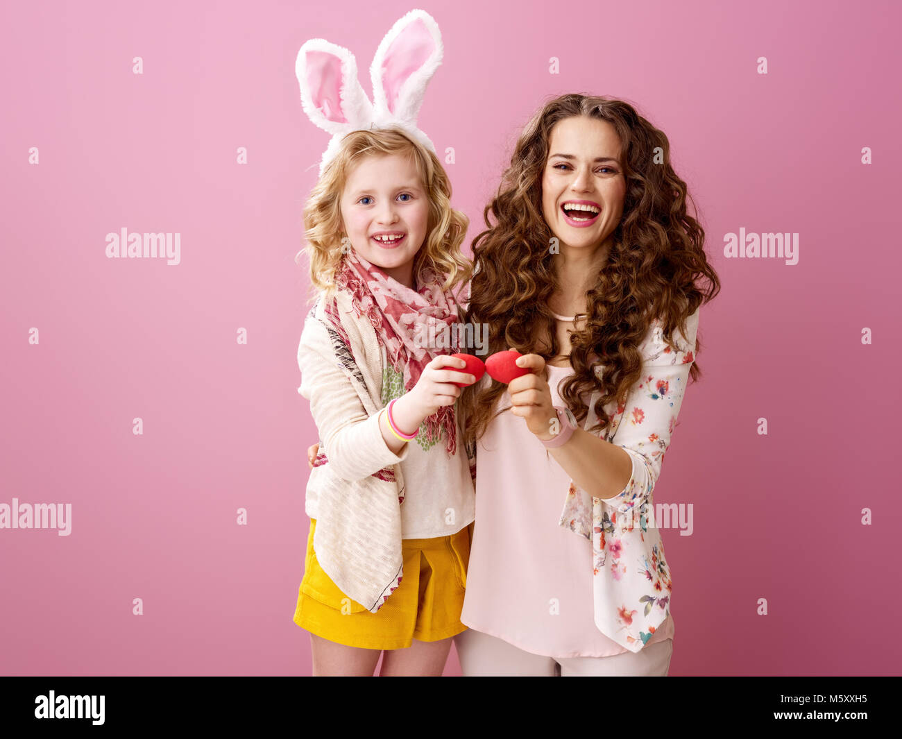 Pink Mood. smiling modern mother and daughter with wavy hair  red Easter eggs tapping isolated on pink - Stock Image