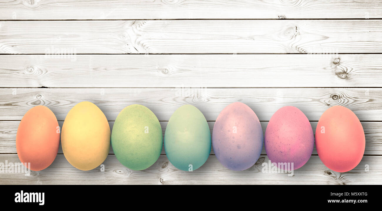Pastel colored eggs on  white wooden planks, panoramic easter background - Stock Image