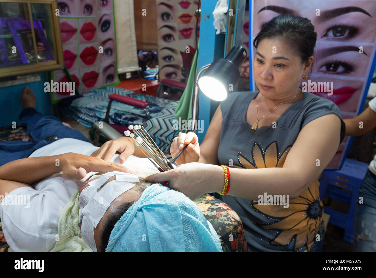 Street beauty therapist doing a facial for a customer, example of Cambodia culture;  Phnom Penh, Cambodia, Asia - Stock Image