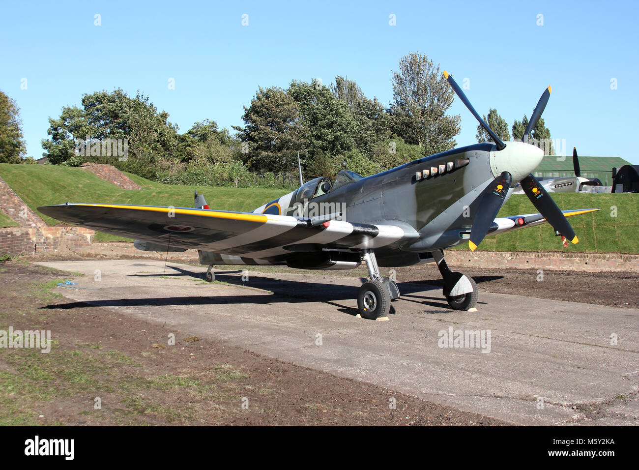 Commonly called 'The Kent Spitfire', Supermarine Spitfire MK IX TA805 sits in one of the wartime revetments - Stock Image