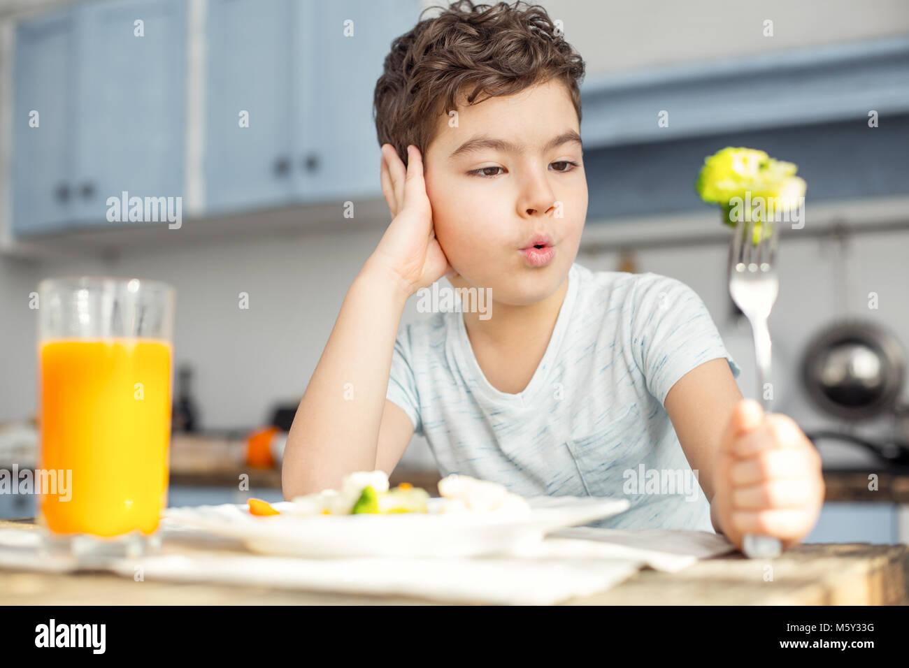 Sad boy eating vegetables for breakfast - Stock Image