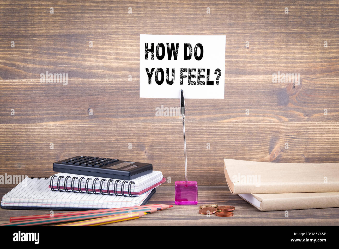 How Do You Feel. Wooden table with stationery - Stock Image