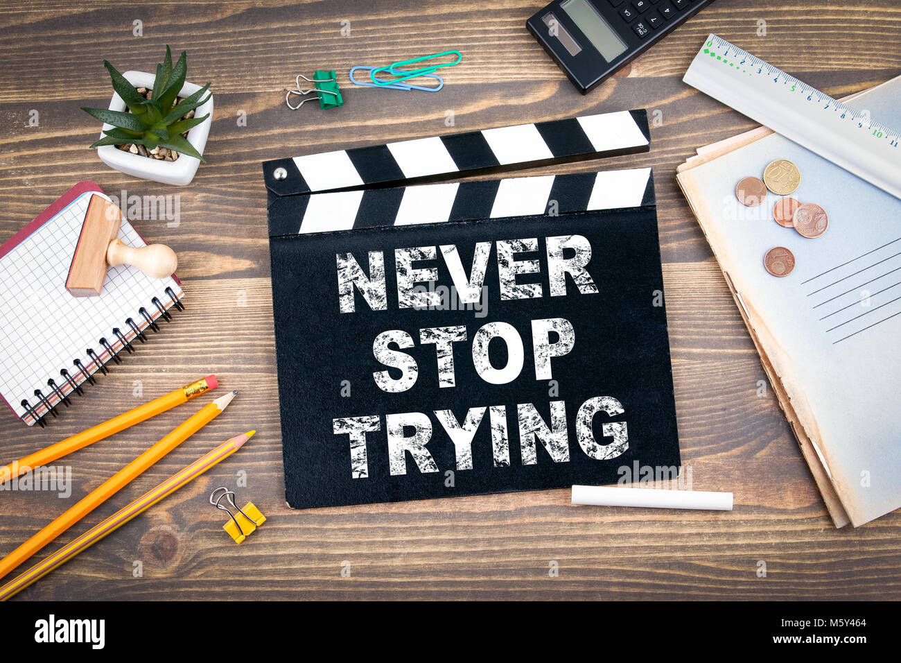 Never stop trying. Movie clapper on a wooden desk - Stock Image