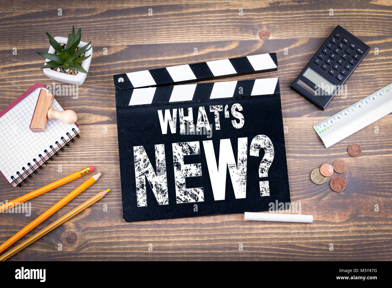 Whats New. Movie clapper on a wooden desk - Stock Image