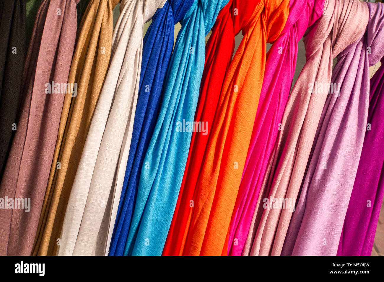 Row of colourful silk scarfs hanging at a market .Colorful fabric background, pink gold and blue color silk fabric - Stock Image