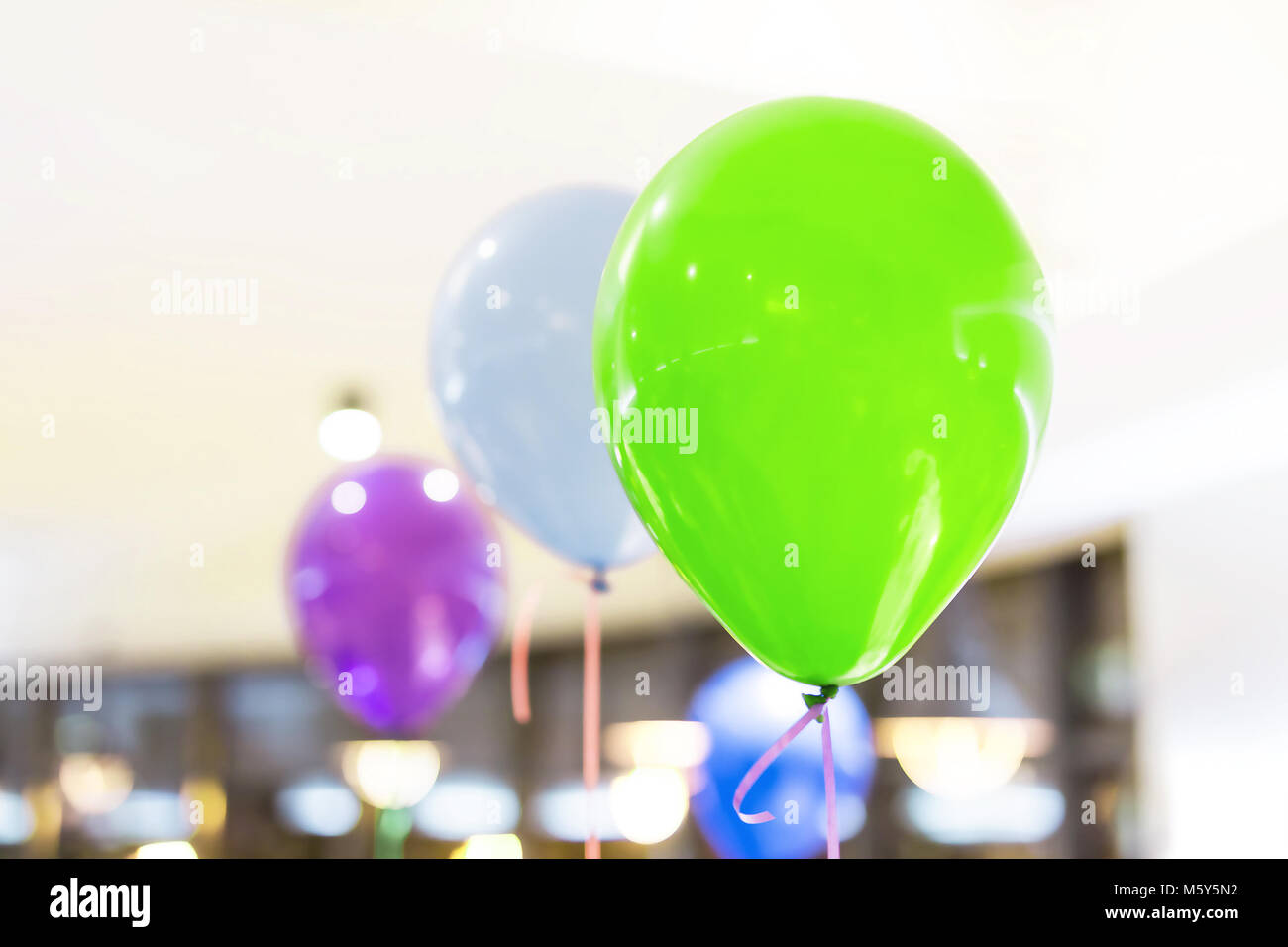 Multicolored air baloons indoor. Preparation for party. Decoration of interior. Children birthday celebration concept - Stock Image