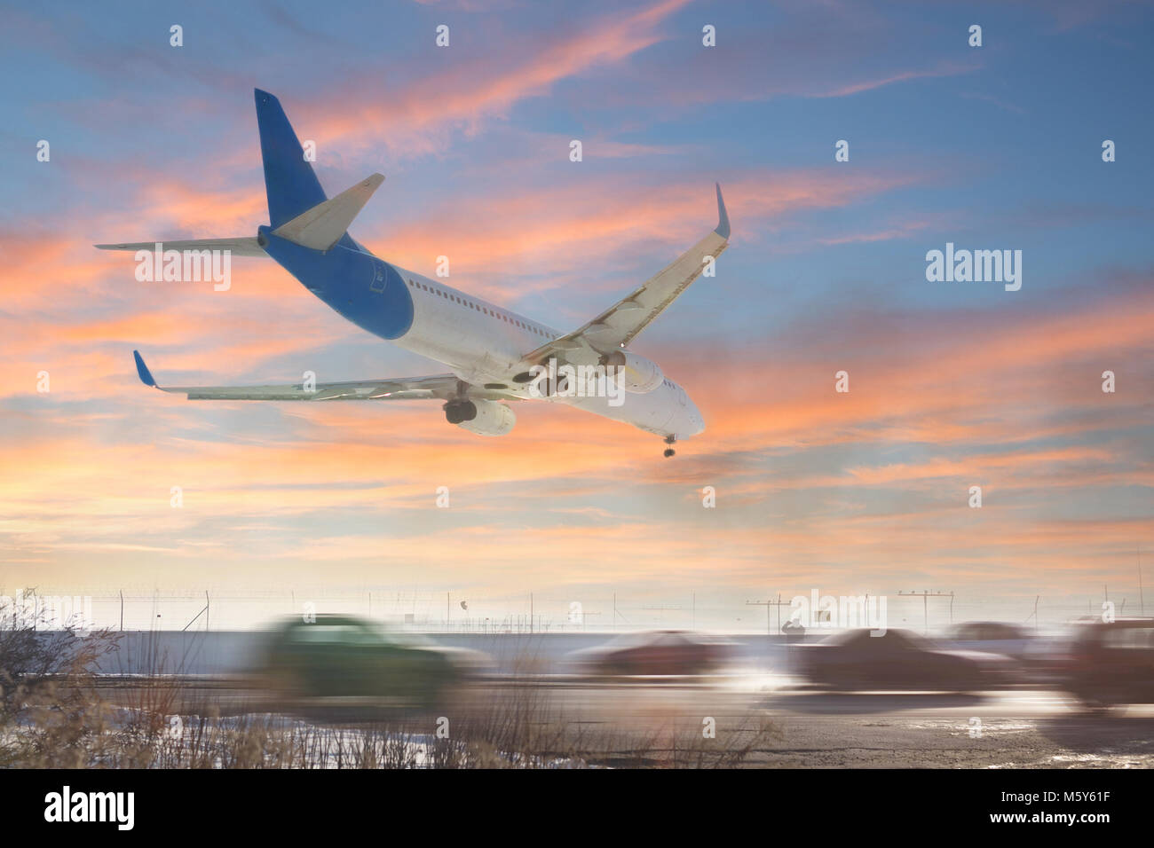 Tail view of landing airplane. Aircraft flying over highway.  Road with high traffic near airport runway. Type of - Stock Image