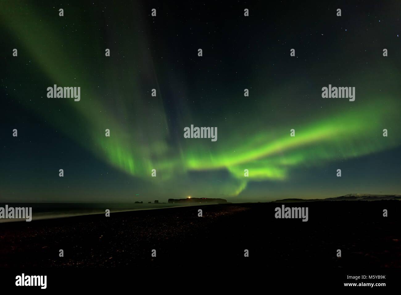 Aurora borealis, or Northern Lights, over Dyrholaey Peninsula and Reynisfjara Beach, Iceland - Stock Image