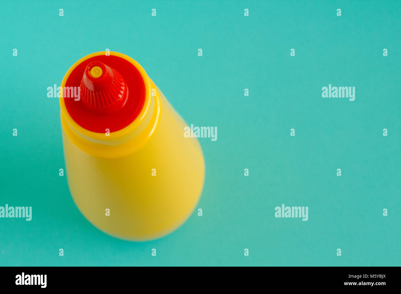 A bright yellow squirting mustard or condiment bottle with bright red twisting lid. Left aligned and viewed from - Stock Image