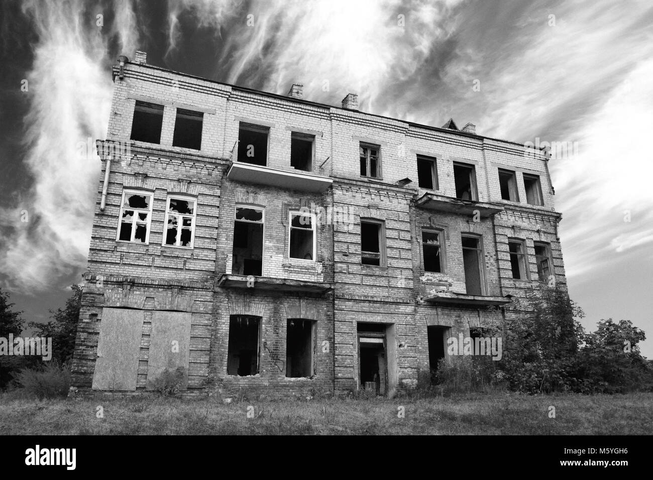 Old abandoned ruined house exterior against dramatic black and white cloudy sky - Stock Image