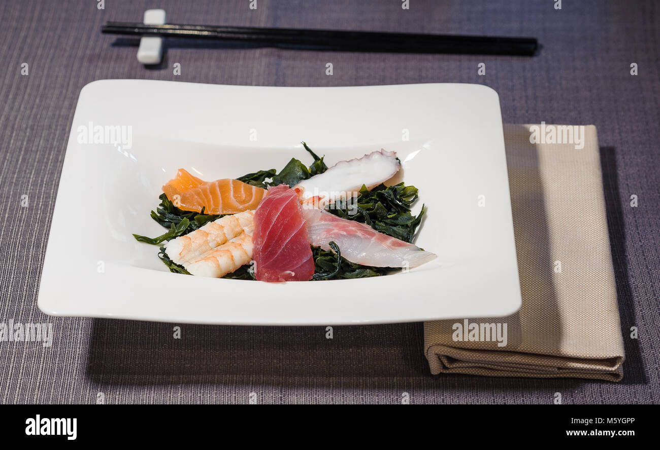octopus, tuna, salmon, swordfish and prawn fillets on bed of seaweeds seasoned with rice vinegar, served on a rectangular - Stock Image