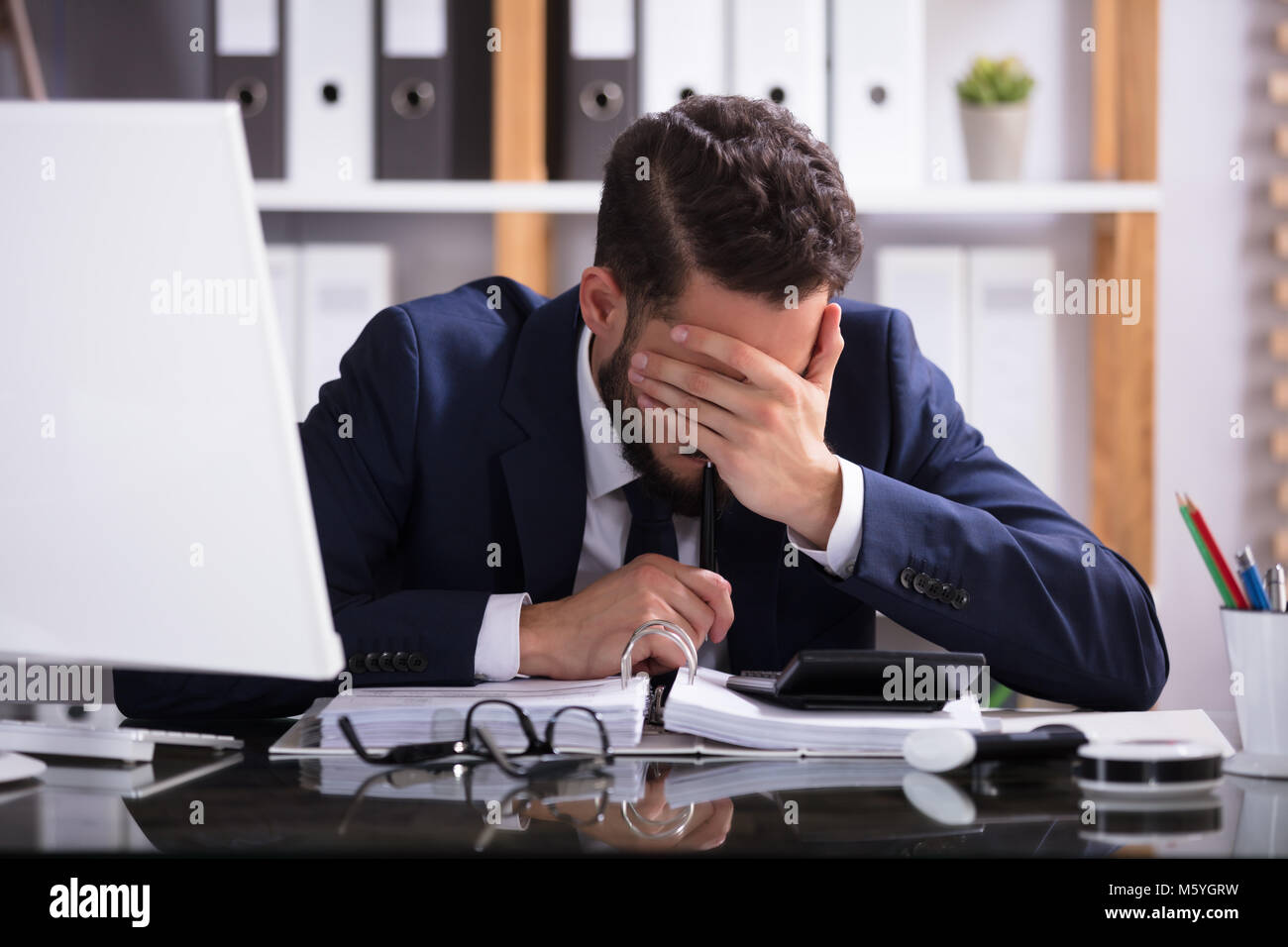 Young Man Suffering From Headache Working In Office With Bill Over Desk Stock Photo