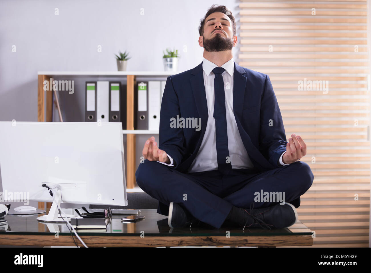 meditation businessman office. Young Businessman Sitting On Desk Doing Meditation In Office