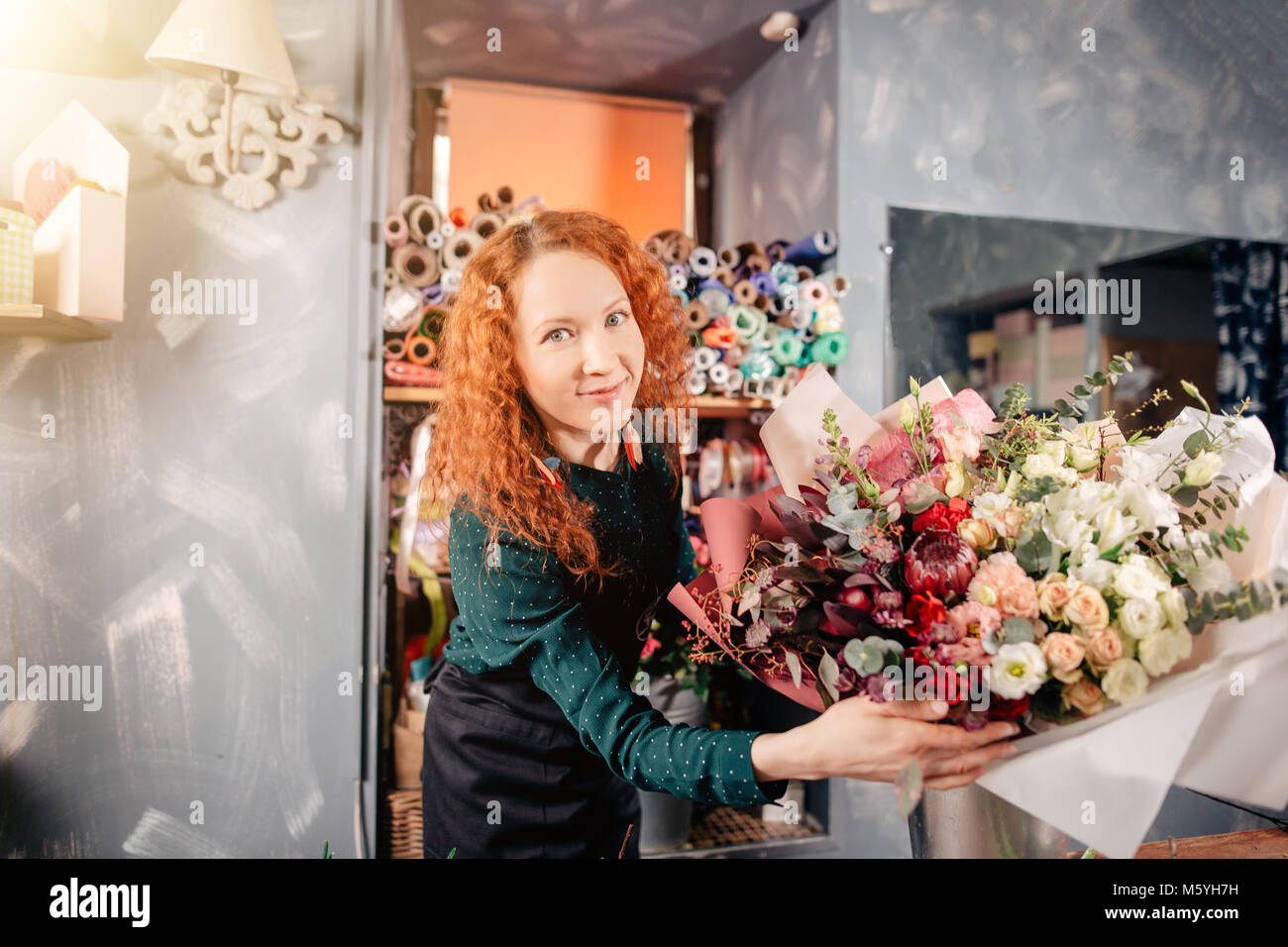 happy shop assistant showing prepared rich floral bouquet at store - Stock Image
