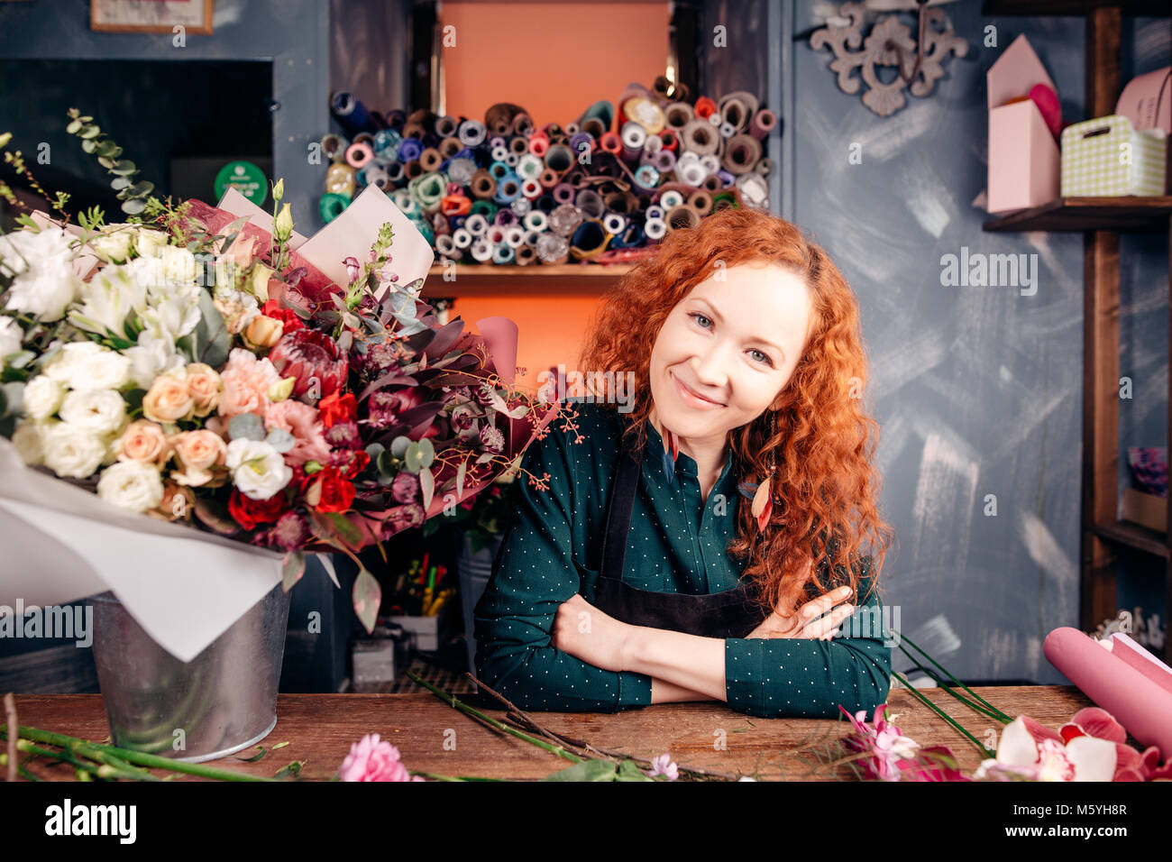 Florist leading small business, sitting beside desk in shop - Stock Image
