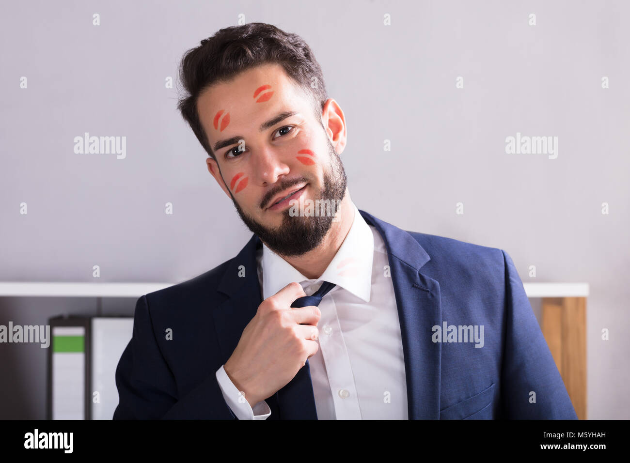 Close-up Of A Young Businessman With Lipstick Kiss Marks On Face - Stock Image