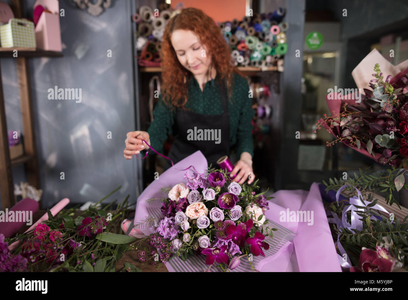 tapping up purple and white bouquet at shop - Stock Image