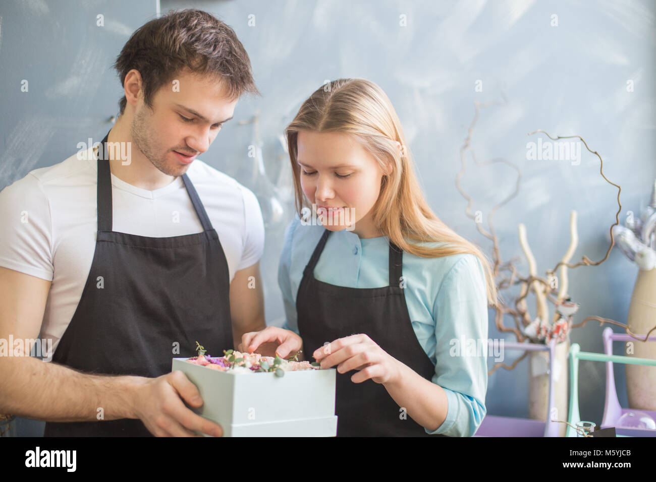 guy and blondy girl looking at box of flowers - Stock Image
