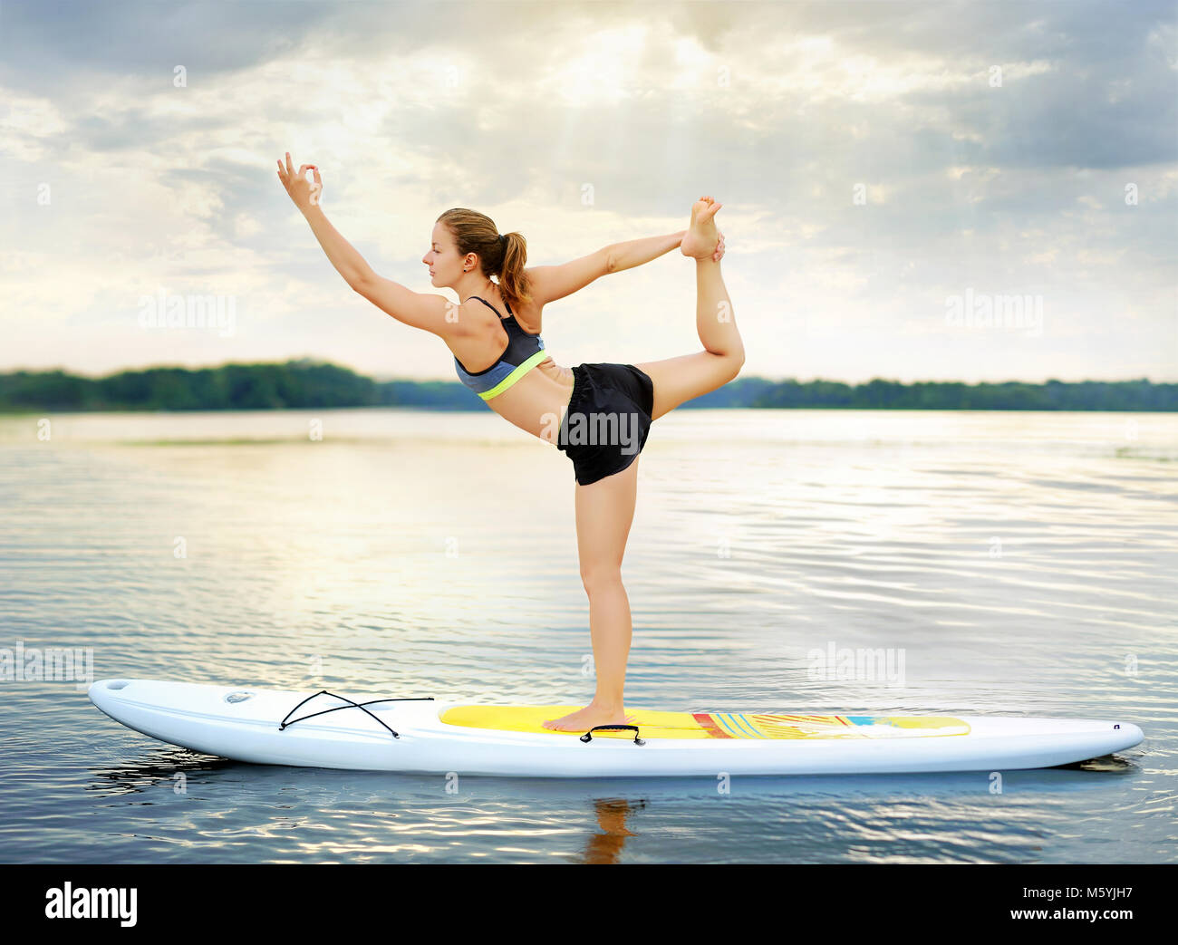Woman practicing Lord of the Dance  yoga Pose balancing on paddle board - Stock Image