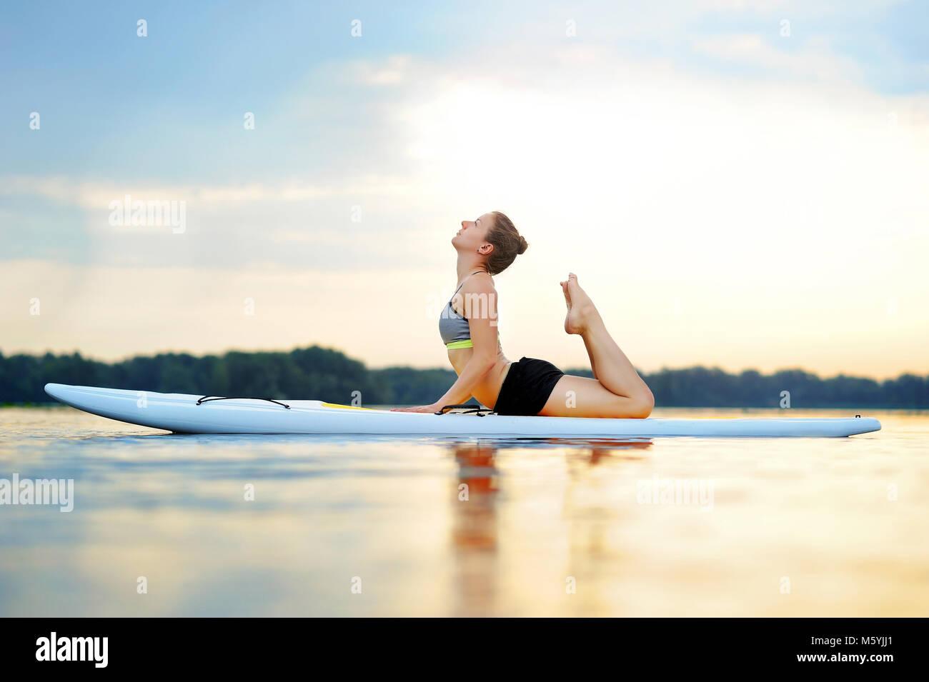 Woman on sup board practicing cobra yoga pose - Stock Image