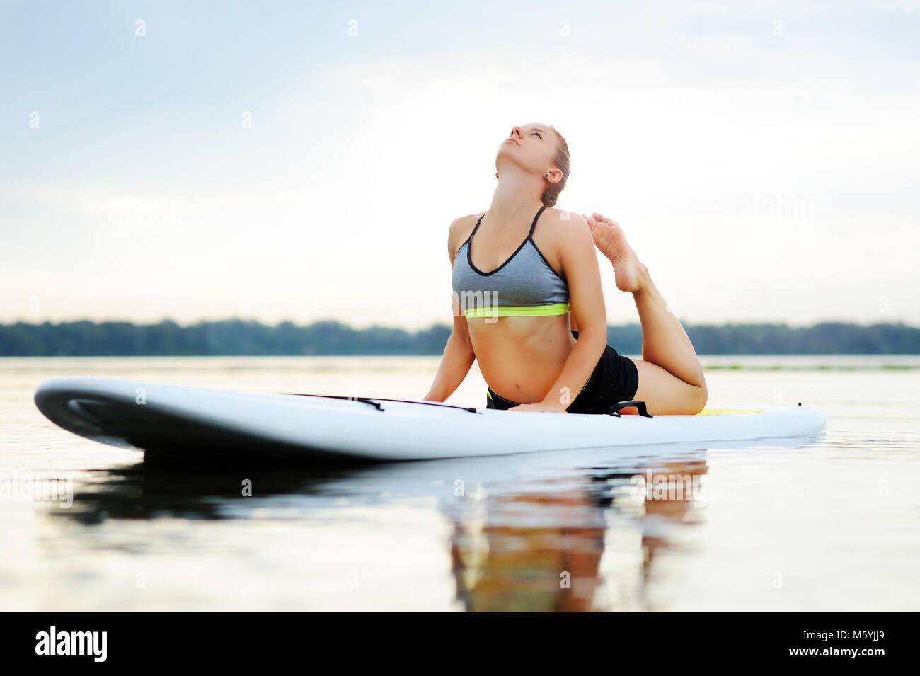 Woman on paddle board practicing snake yoga pose - Stock Image