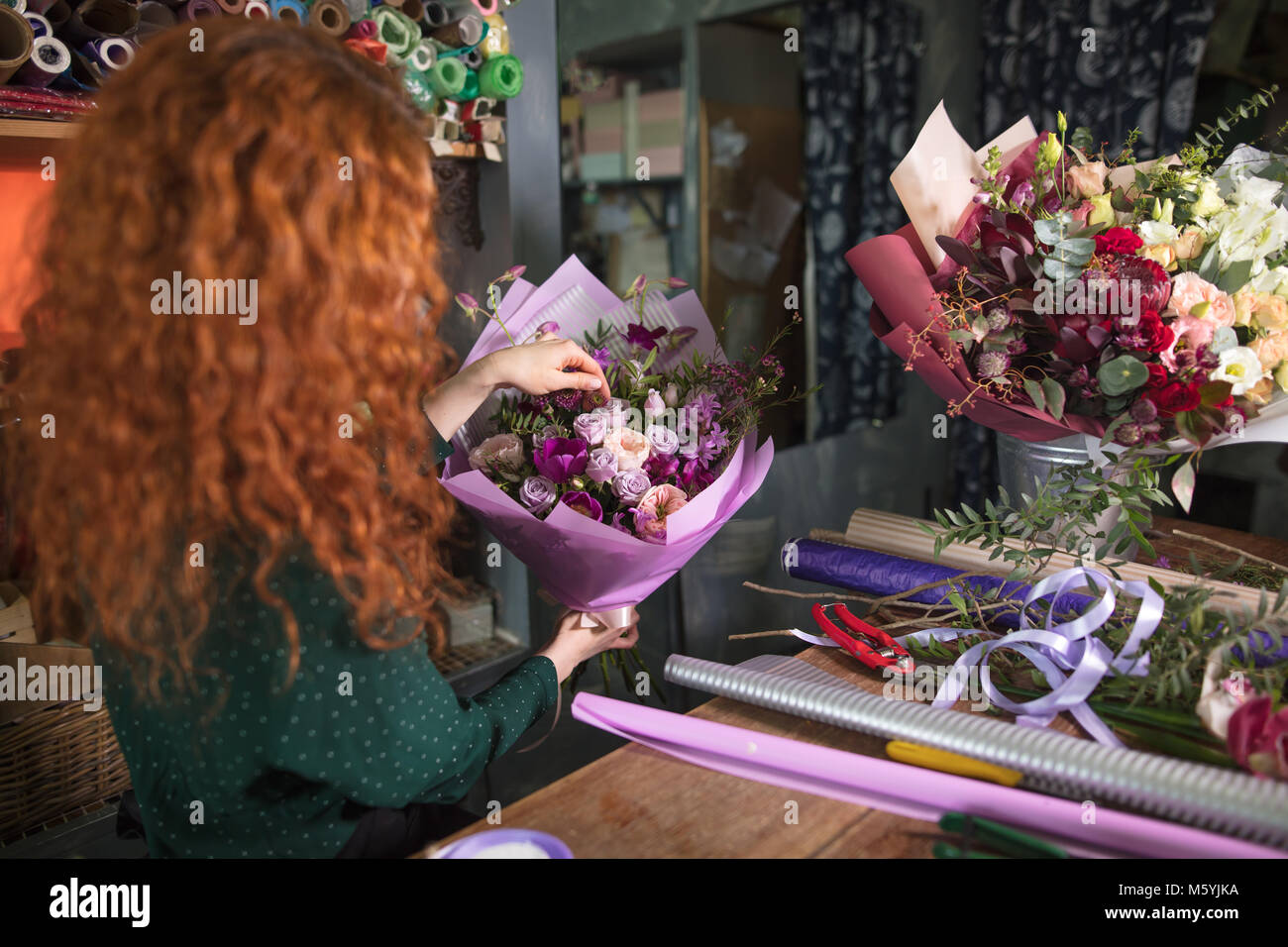 woman near the table with wrappers for flowers - Stock Image