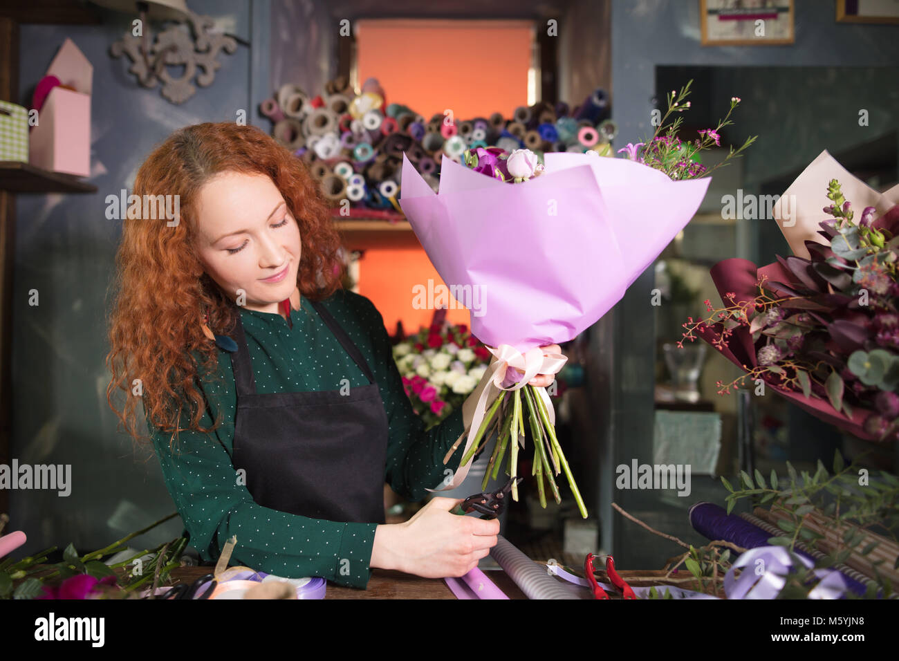 highly skilled florist cutting a flower stalk - Stock Image
