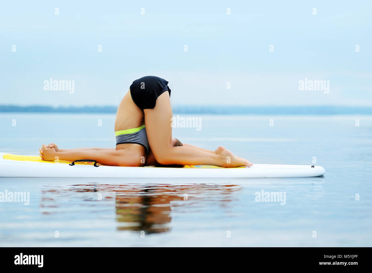 Woman practicing  Ear Pressure yoga Pose on paddle board Stock Photo