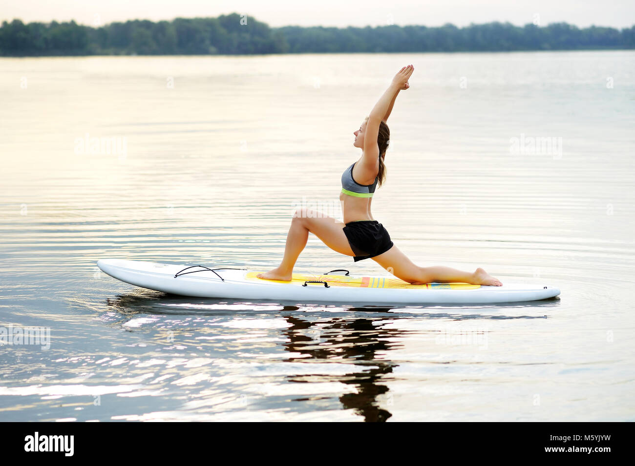Woman practicing Crescent Lunge yoga Pose on the paddle board in the morning - Stock Image