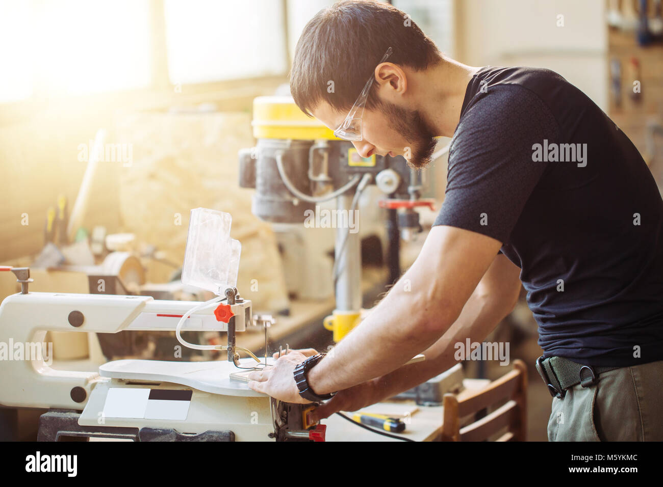 Carpenter engaged in processing wood at the sawmill. - Stock Image