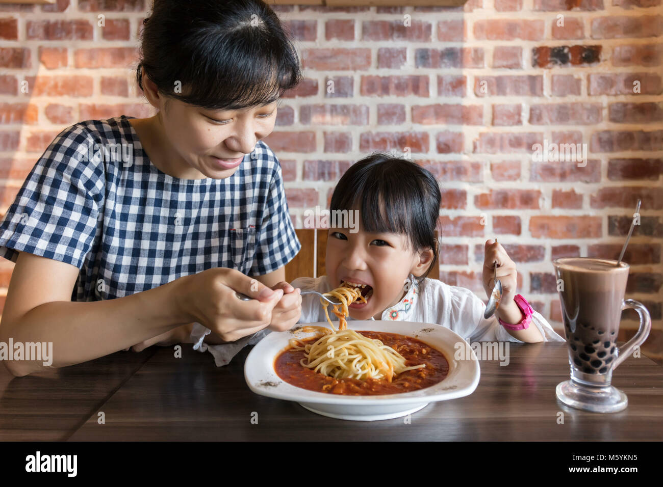 Asian Chinese mother and daughter eating spaghetti bolognese in the restaurant - Stock Image