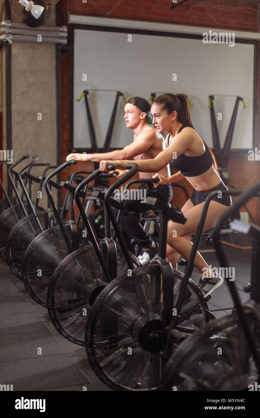 woman and man biking in gym, exercising legs doing cardio workout cycling bikes - Stock Image
