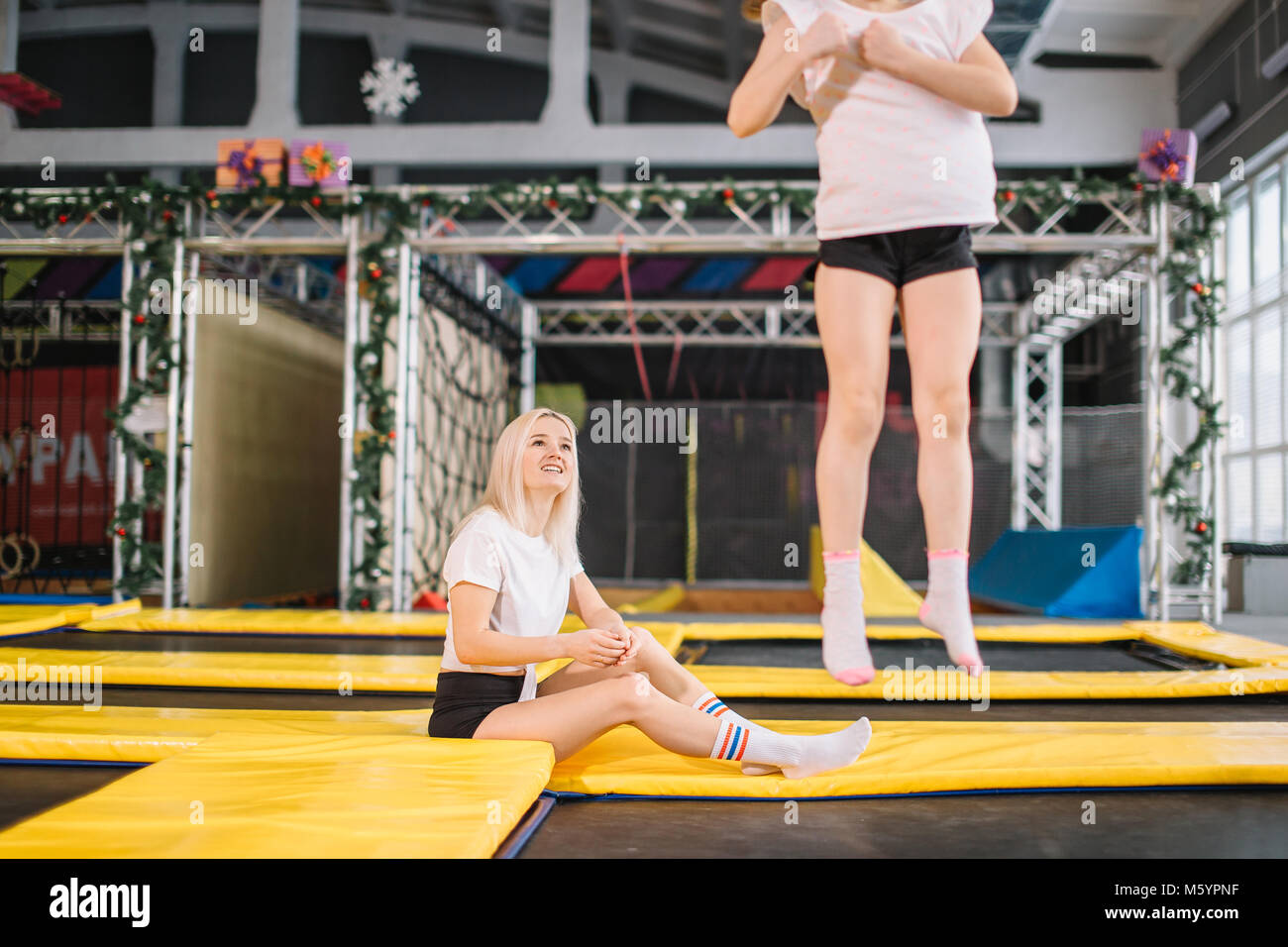 daughter Bouncing On Trampoline while Mother watch for safety - Stock Image