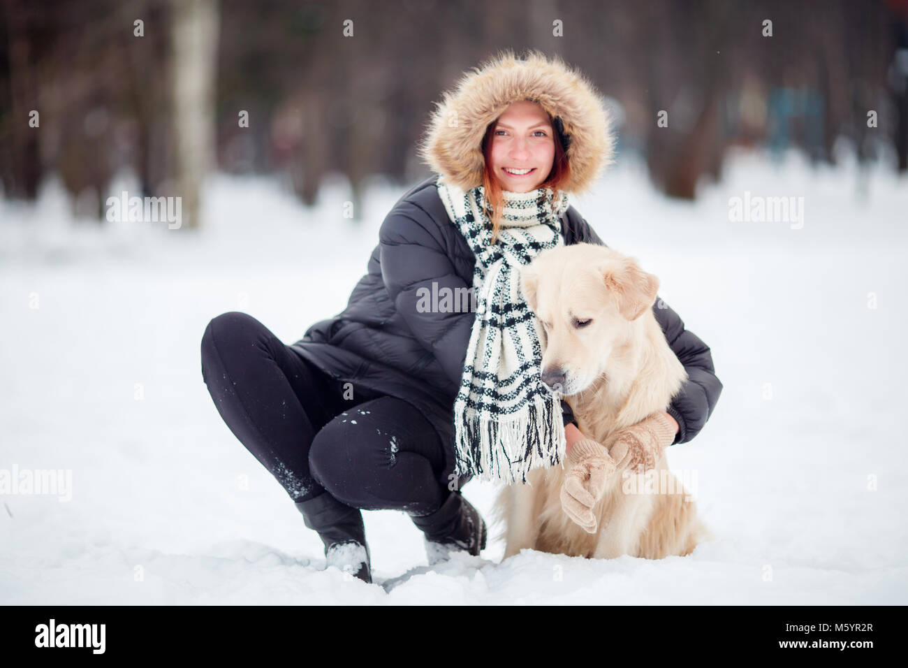 Image of girl in black jacket squatting next to dog in winter - Stock Image