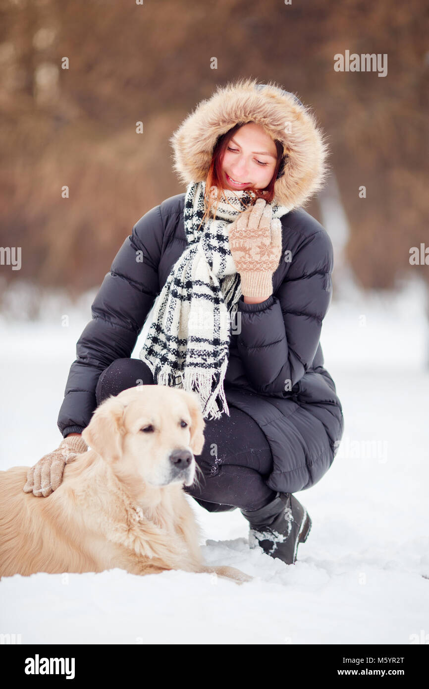 Photo of happy woman squatting next to labrador in winter - Stock Image