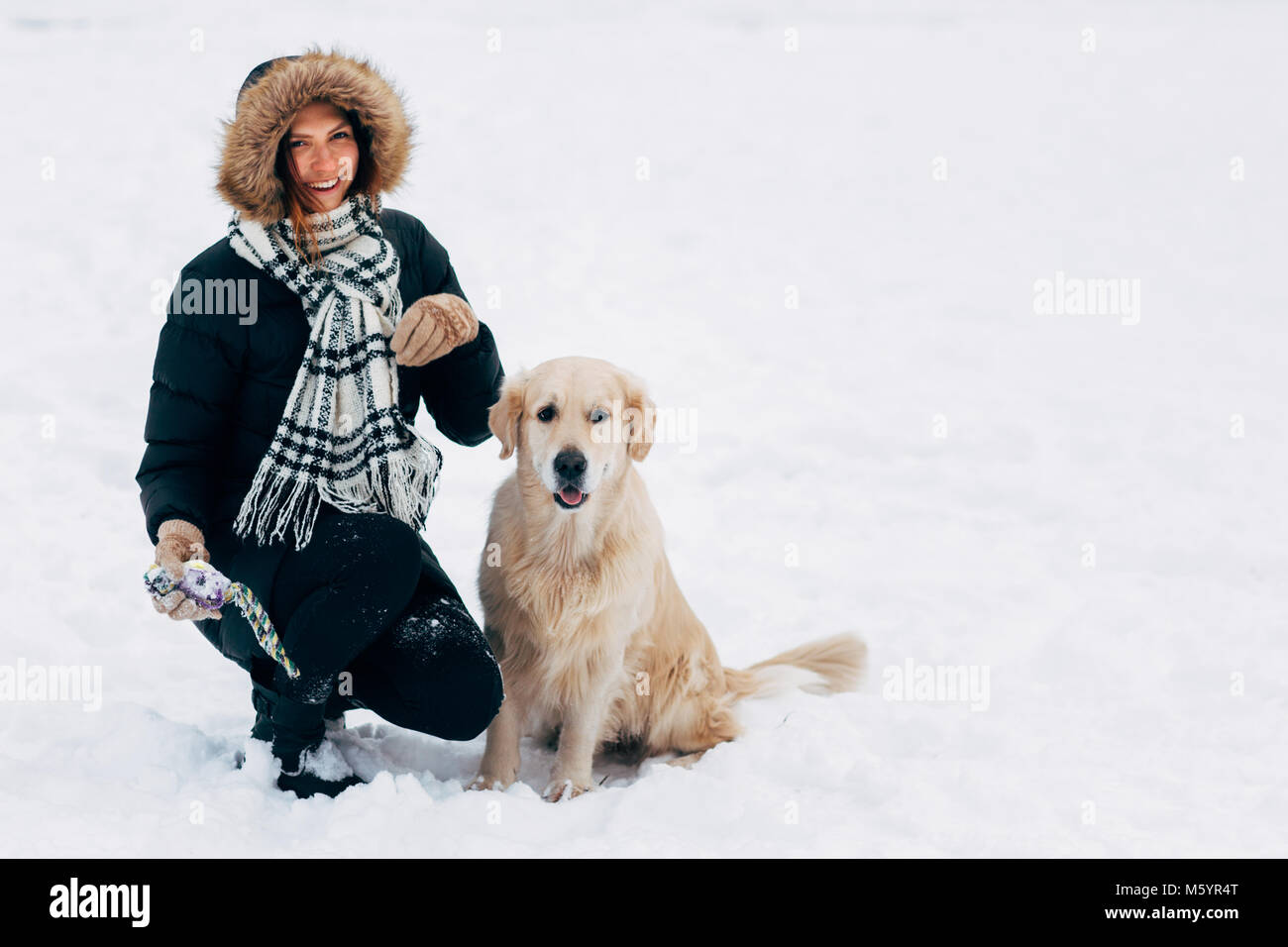 Photo of smiling girl with dog in winter park - Stock Image