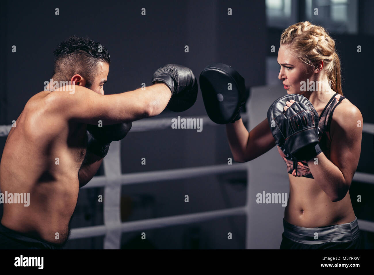 Sporty muscular young man and woman boxing together isolated on black - Stock Image