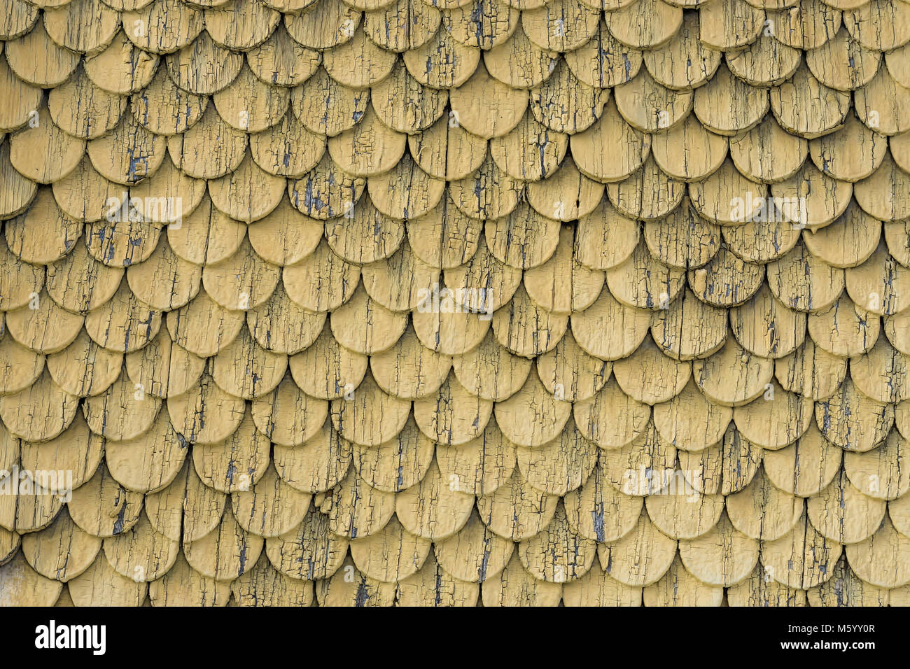 Old rustic wood tiling roof wall texture. Yellow weathered background. - Stock Image