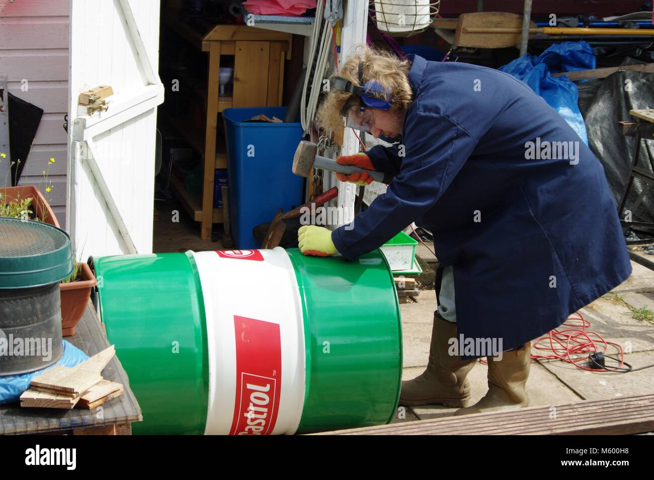 Teenager with long Blonde Hair, a Lab Coat and Safety Equipment Hammering Holes into a Used Oil Drum. DIY Project, - Stock Image