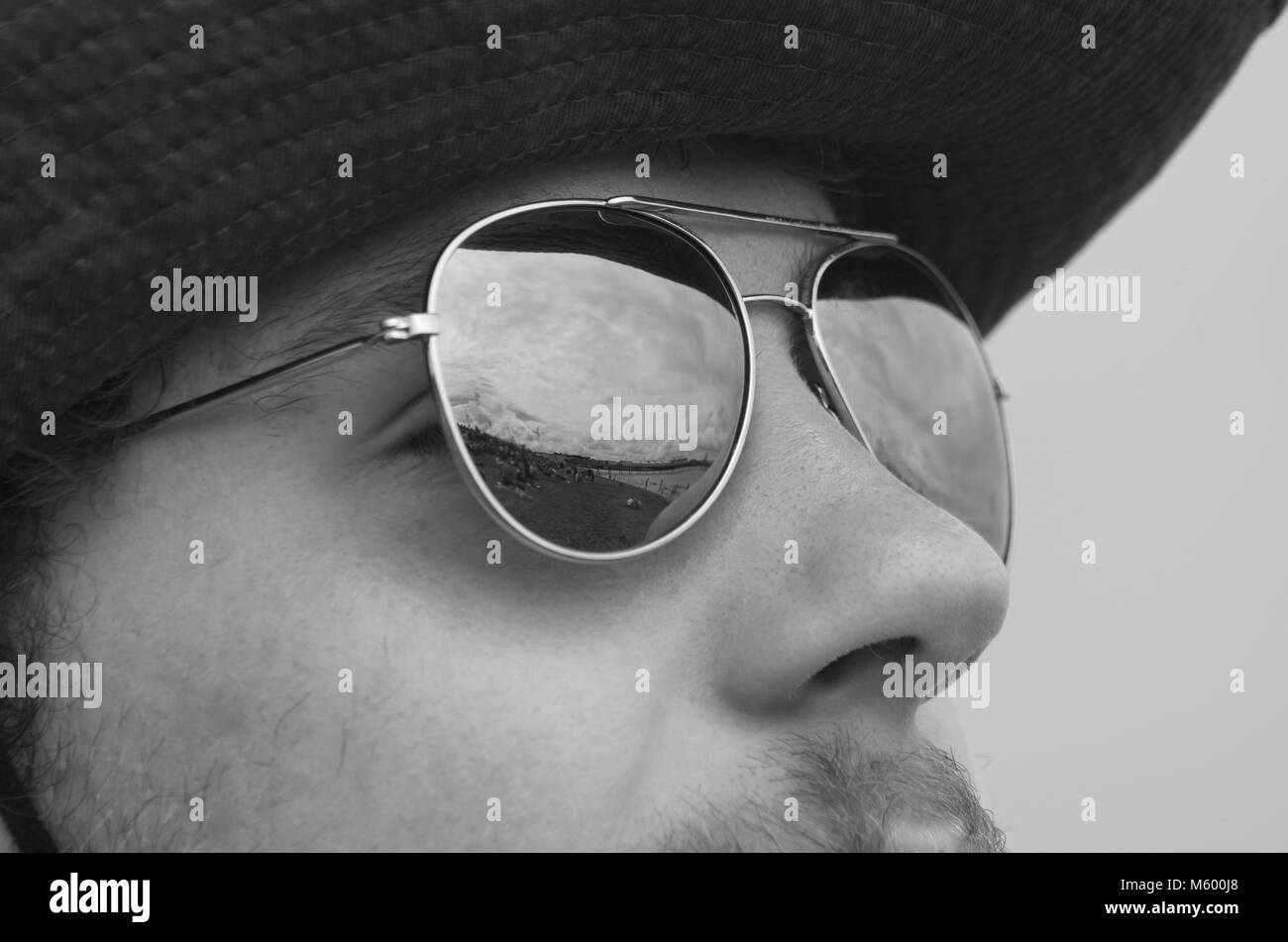 Young Trendy Man, Wearing Aviator Sunglasses and a Hat on a Summer Day. Black and White Photo. South Devon, UK. - Stock Image