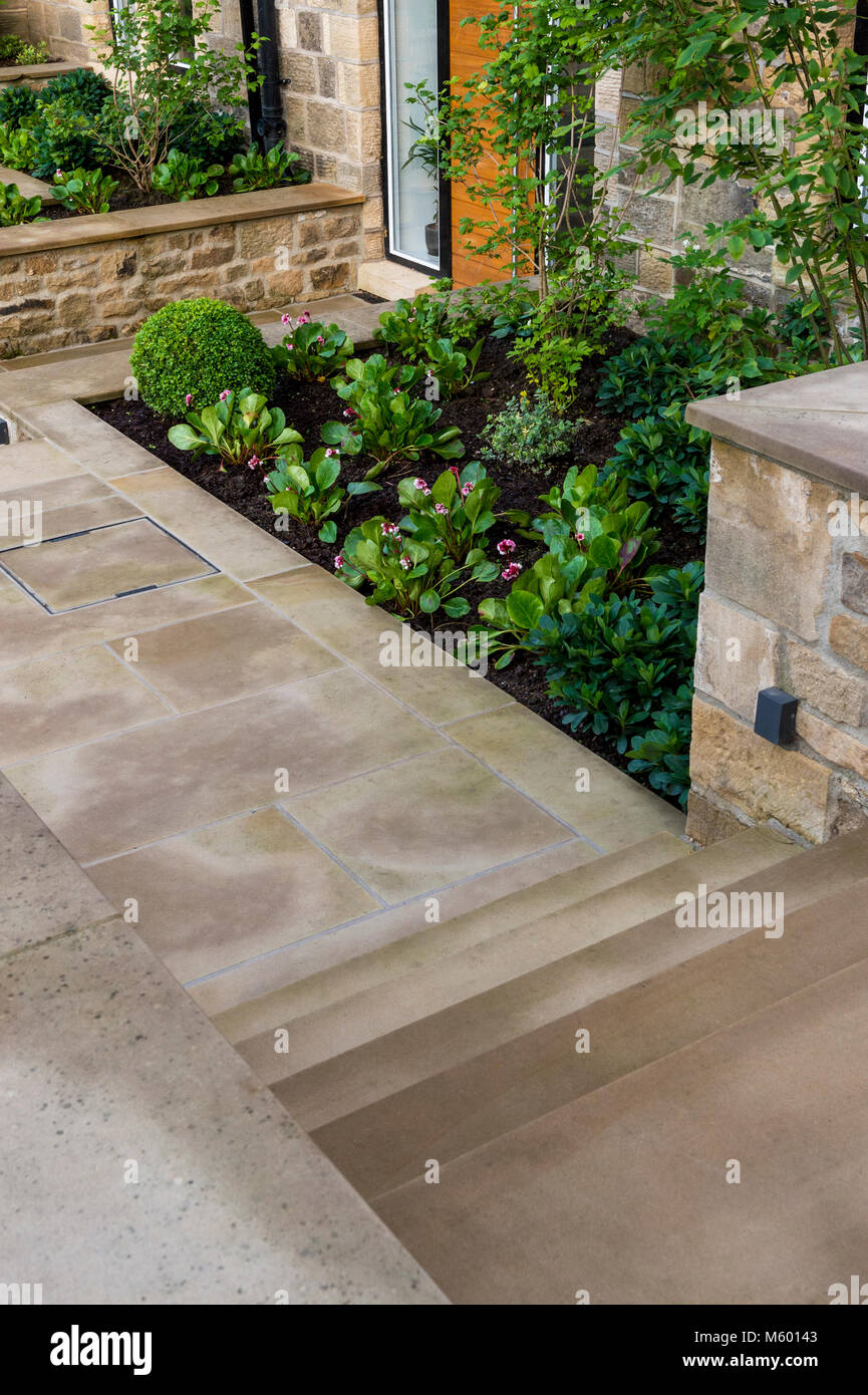 Small corner of beautiful, landscaped, private garden with contemporary design, paved path & steps, border shrubs Stock Photo