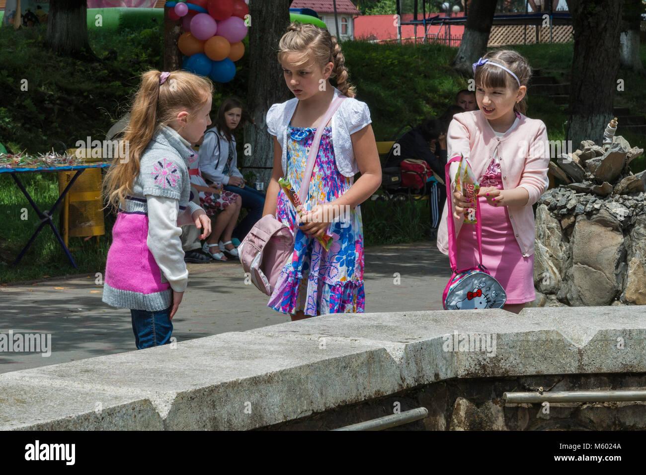 Girls at fountain in town of Yaremche, Carpathian Mountains, Hutsul Region, Pokuttya, Prykarpattia Region, Ivano - Stock Image