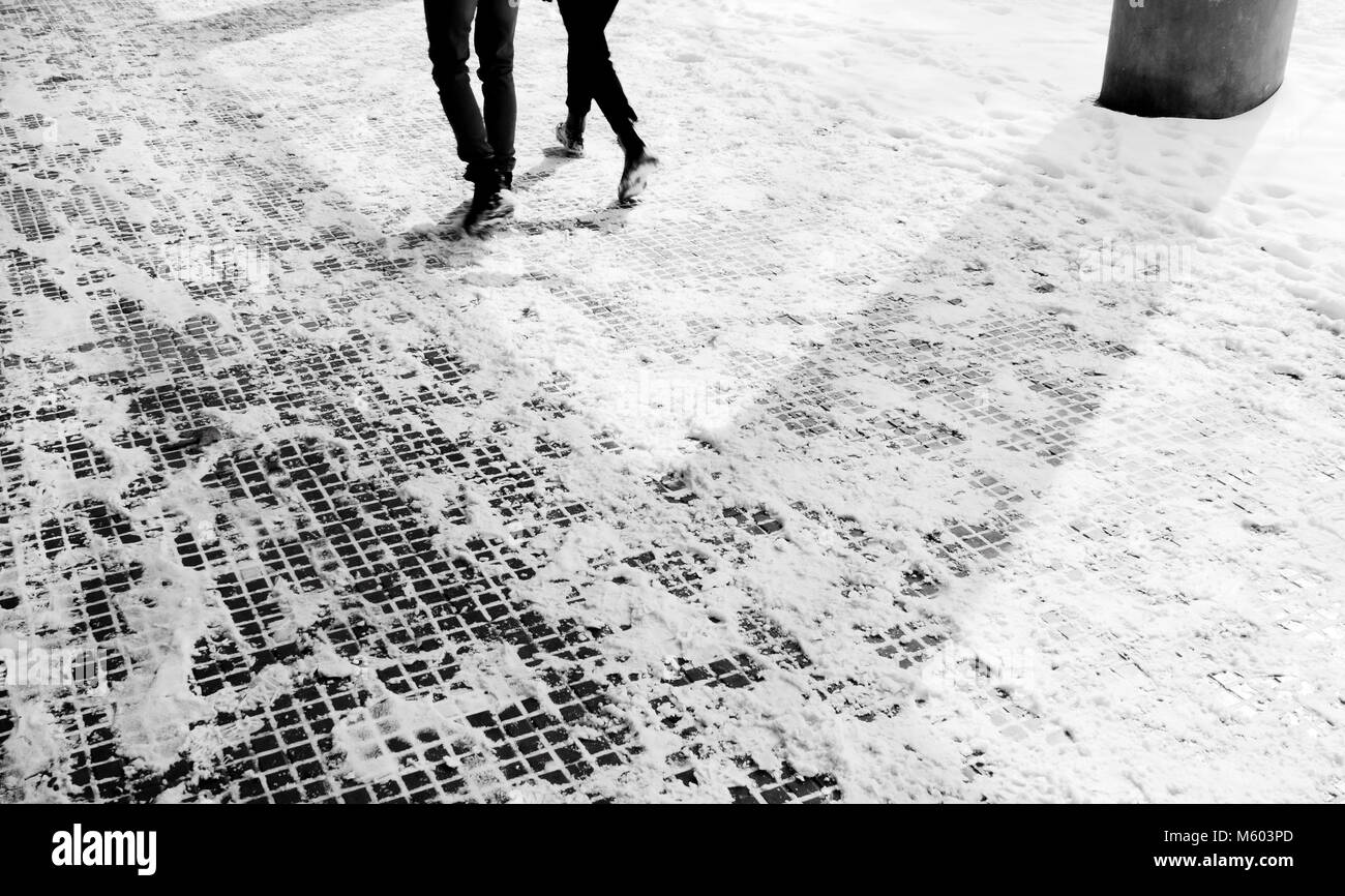 Legs of two people walking down the snowy sidewalk in motion blurin black and white - Stock Image