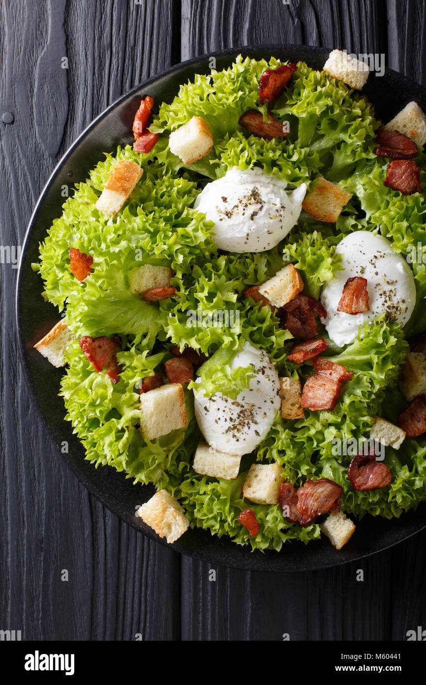 Organic French Lyonnaise salad with lettuce, bacon, croutons and poached eggs close-up on a plate on the table. - Stock Image