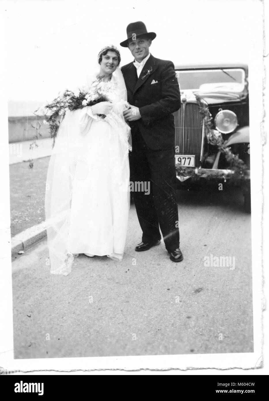 1960s 1970s wedding caucasian couple looking at camera posing in front of an ancient car. Black and white shot. - Stock Image