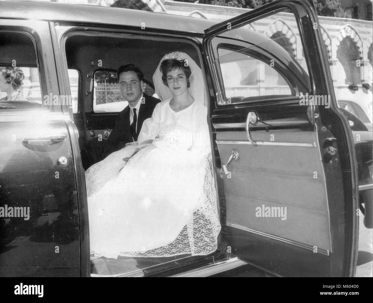 1960s 1970s wedding caucasian couple looking at camera posing inside an ancient car. Black and white shot. Italy - Stock Image