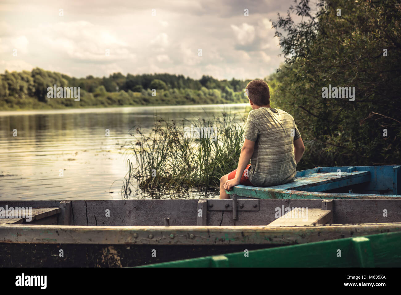 Teenager boy lonely contemplation countryside scenery on river boat during countryside summer holidays - Stock Image
