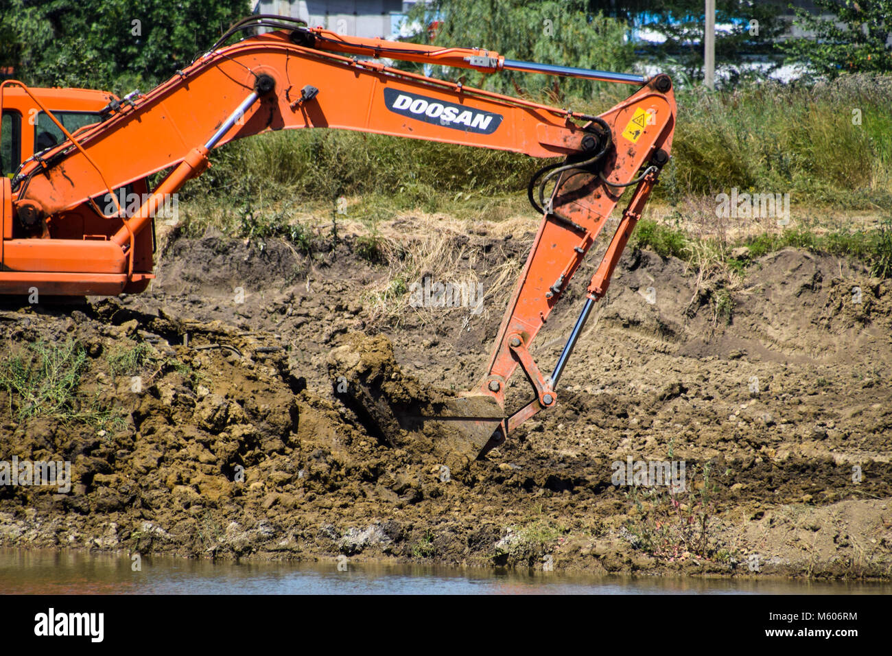 Excavator digs clay in the Quarry with clay. Extraction of clay. - Stock Image